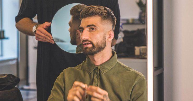 Friseur prüft Hinterschnitt mit Spiegel