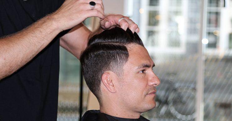 Mann, der sich vom Friseur die Haare stylen lässt