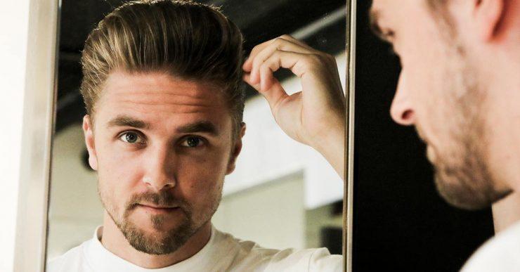 Mann, der seine Haare im Spiegel stylt